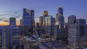 A high wide angle shot of Downtown Minneapolis cityscape illuminating during twilight 4K UHD Timelapse. A wide angle twilight cityscape timelapse shot of stock footage