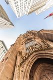 Wide angle upward view of Trinity Church at Broadway and Wall Street with surrounding skyscrapers, Lower Manhattan, New Royalty Free Stock Images