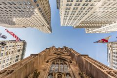 Wide angle upward view of Trinity Church at Broadway and Wall Street with surrounding skyscrapers, Lower Manhattan, New Royalty Free Stock Image