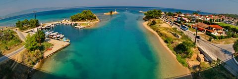 Wide angle view of a blue sea and houses. A picture of a blue sea and small yachts ,a distant islet and small houses nearby,in an area in Greece,Halkidiki,in a Stock Image