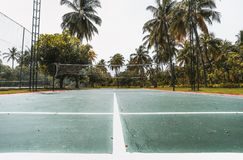Wide-angle view of badminton court, Maldives. Wide-angle view from the bottom of badminton court on a summer day: green and red field with marking on the ground royalty free stock image