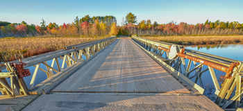 Wide angle view, bridge over Corry lake, late afternoon sunshine. Royalty Free Stock Photo