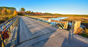 Wide angle view, bridge over Corry lake, late afternoon sunshine. Royalty Free Stock Photos