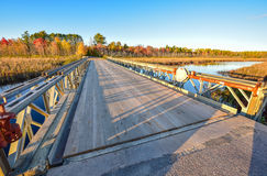Wide angle view, bridge over Corry lake, late afternoon sunshine. Royalty Free Stock Images