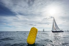 Buoy and sailing boat in the sea Royalty Free Stock Images