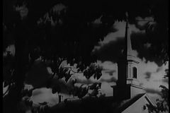 Wide angle view of church steeple from behind tree stock footage