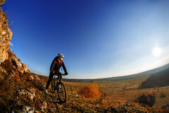 Wide angle view of a cyclist riding a bike on a nature trail in the mountains. Royalty Free Stock Photo