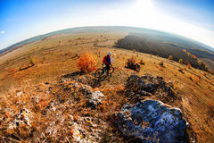 Wide angle view of cyclist standing with mountain bike on trail at sunrise Royalty Free Stock Photos