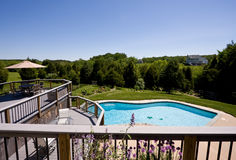 Wide angle view of deck and swimming pool. Modern deck and swimming pool in expansive landscaped garden stock images