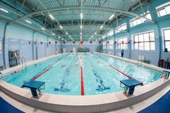 Wide angle view at four lines swimming pool for a children groups. Blurred background, focus is on foreground. Wide angle view at four lines swimming pool for Stock Image
