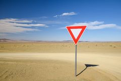 Wide angle view of a give way yield sign at a gravel road intersection in the Namibian Desert between Ai-Ais Fish River Canyon a. Nd Aussenkehr. Mountains in the Stock Image