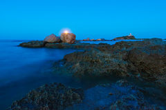 Wide Angle View of Moon over Seascape, Rocks and Lighthouse. Gold hour over the wild rocky beach coastline and the sea. Lighthouse, moon and rocks at night wide stock images