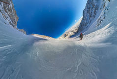 Wide-angle view of a mountain hiker to climb a mountain of snow. Couloir Royalty Free Stock Photos