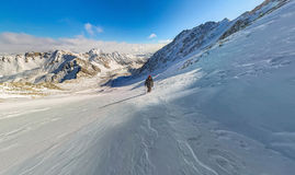 Wide-angle view of a mountain hiker to climb a mountain of snow Stock Image