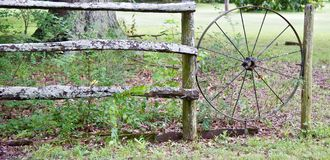 Chuck Wagon Wheel. Wide Landscape view of Old Wooden Chuck Wagon wheel that has been built into a wooden hand constructed fence Royalty Free Stock Photos