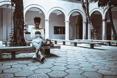 Brazilian young undergraduate girl in university courtyard with. Wide-angle view of a pensive cute African-American female student who is sitting on the concrete Royalty Free Stock Photo
