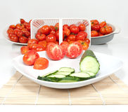 Wide Angle View of Plated Tomatoes. A wide angle studio view of two sliced field tomatoes and a cucumber and a basket and dishes of ripe field tomatoes with the Royalty Free Stock Photos