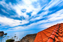 Wide angle view from the roof of red tiles to landscape. Dramatic sky with storm clouds over sea. Royalty Free Stock Image