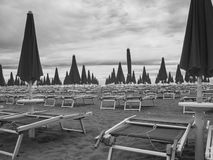 Sun loungers. Rows of unoccupied Sun loungers and parasols on the empty beach royalty free stock image