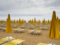 Sun loungers. Rows of unoccupied Yellow Sun loungers and parasols on the empty beach stock photos