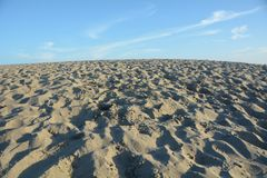 Wide-angle view of sand dune at Pacific City, Oregon Coast. This is a wide angle view of a sand dune at Pacific City on the Oregon coast under a blue sky Royalty Free Stock Photography