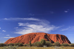 Wide angle view showing Uluru against a vivid blue sky with white clouds above the rock. Royalty Free Stock Images