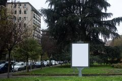 Wide angle view of a small blank white advertising billboard in the city park royalty free stock images