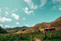Two forsaken houses in mountains. Wide-angle view of summer landscape: old metal gates with feeding ground behind, shepherd`s house and abandoned shack, hills Royalty Free Stock Images