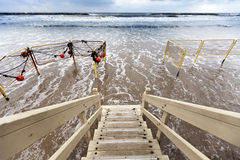 View from the Lifeguard Hut. Wide angle view of the tides at the beach on a stormy winter day, as seen from the top of the stairs belonging to a lifeguard hut Royalty Free Stock Photos