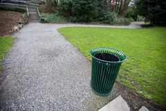Wide angle view of trash can by a path in a park Stock Photography