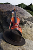 Wide Angle View of Violin and Cowboy Hat Lying. On rocks by the Ocean Royalty Free Stock Image