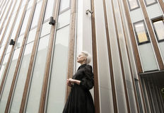 Wide angle view, woman in long black dress with short white haircut, building. Wide angle view, woman in long black dress, building Stock Images