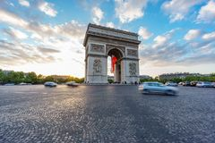Wide Arc de Triomphe and blurred traffic at sunset. Dusk time with dramatic sky behind Arc de Triomphe and blurred cars traffic along the Champs-Elysees traffic Royalty Free Stock Images