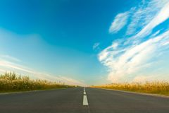 Wide Asphalt Gray Road On Bright Blue Sky Background. Wide Asphalt Gray Road On Bright Blue Sky Background With Clouds In Spring Stock Photo
