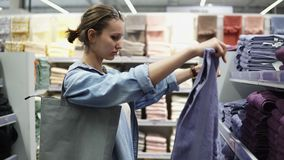 Wide assortment of different colors bath towels. Side view of a female buyer between the rows. Unfolds the towels. Selecting. Supermarket stock video
