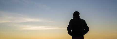 Wide backlit view on person with hands in pockets. Over calm early evening or morning sky. Includes copy space royalty free stock photography