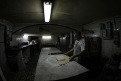 Wide Baker at work on antique bakery factory and store Royalty Free Stock Photo