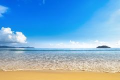 Wide beach with golden sand shore and blue sky stock photos
