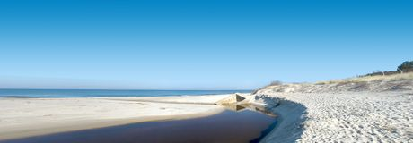 Wide beach panorama. Empty beach, interesting water stream, some concrete blocks remains. Clear blue sky. The Baltic Sea Stock Image