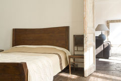 Wide bed near door. And chair Stock Photography