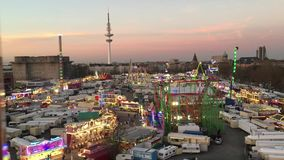 Wide Bird`s Eye Shot of large Fun Fair `Hamburger Dom` from Ferris Wheel with Roller Coaster and Carnival Rides at dusk stock video footage