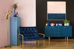Wide armchair in living room. Wide, blue armchair in a pastel living room interior with a cabinet and painting on a black wall stock photos