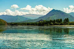 The wide blue river flows in the mountains on a summer day Royalty Free Stock Photos