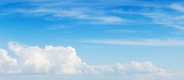 Wide blue sky, panoramic background photo. White cumulus and cirrus clouds formation royalty free stock images