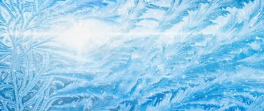 Wide blue winter background, frozen icy window, weather forecast royalty free stock images