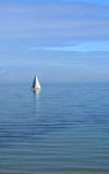Wide Blue Yonder. Single white-sailed yacht sailing on a calm sky-blue sea - portrait view royalty free stock image