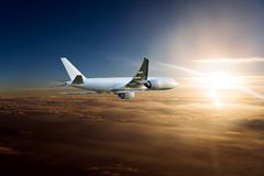 Wide body cargo plane in flight. Aircraft flies high above the clouds towards the sun Royalty Free Stock Image