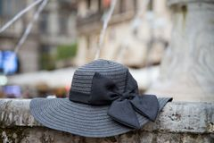 Black women`s hat with bow, in place outside fountain royalty free stock image