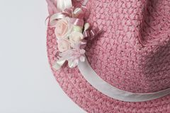 A wide-brimmed female hat of coral color, decorated with a buttonhole. Artificial flowers in the form of roses. Royalty Free Stock Image
