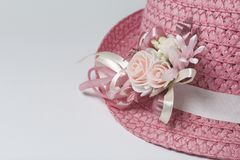 A wide-brimmed female hat of coral color, decorated with a buttonhole. Artificial flowers in the form of roses. Stock Photos